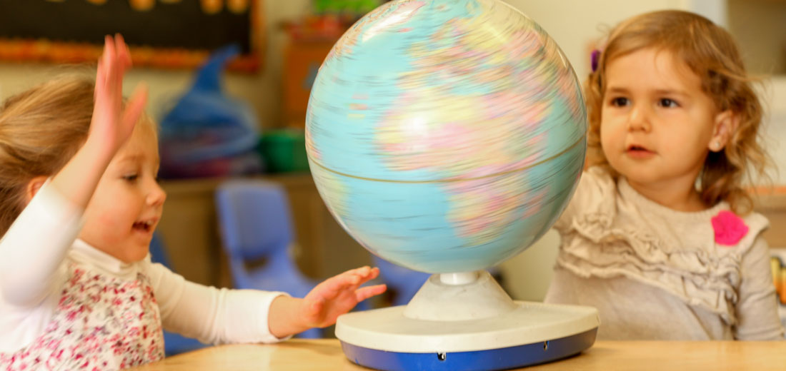 girls playing with globe